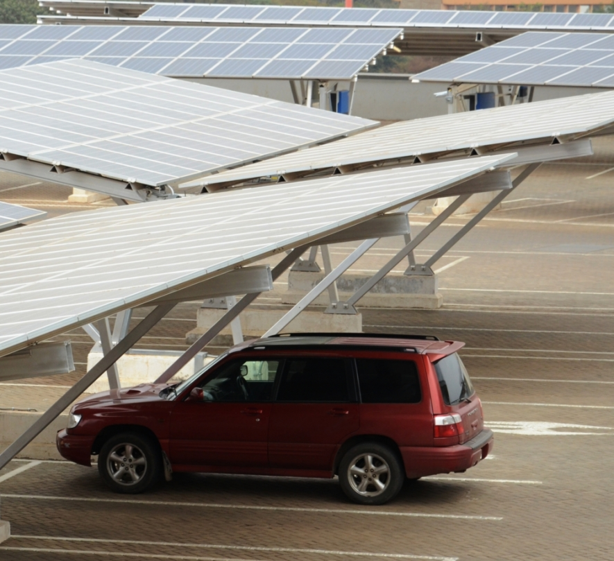 A car is  parked under solar panels at a solar carport at the Garden City. Solarcentury installed the solarcarport system to save on power bills.